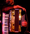 Loved the light on that accordion. Performer just listening to the band...