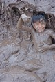 Young boy playing on the muddy bank of of the TonleŽ Sap River. Cambodia