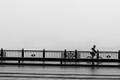 Cyclist on the bridge in foggy morning