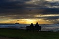 A couple enjoys a beautiful tropical Hawaiian sunset on the island of Oahu, Hawaii