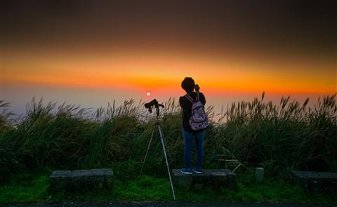 Girl capture a photograph of sunset