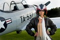 Model Carole M. stands in flight gear in front of a North American T-6 Texan trainer aircraft at an airfield near Gulfport, MS.