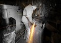 In the western town Kula in Turkey, a Blacksmith is grinding a piece of metal with sparks flying off.