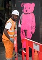 Construction worker protecting a picture of a pink bear in London.