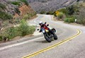 A modern girl ripping up the Malibu canyons on a motorbike with stylish safety attire and glasses.