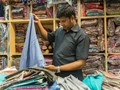 Penang shop employee folding saris