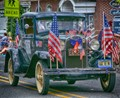 Antique car with several American flags
