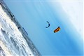 Two kiteboarders surfing waves