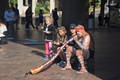 A didgeridoo player invites his audience to participate in Sydney.