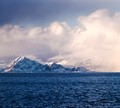 Mt Steinetind on Lofoten Island, Norway, about to be engulfed by a snow storm. The city of Stamsund on the left is already socked in.