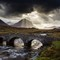 A couple crossing the old bridge at Sligachan