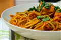 Shrimp pasta with fresh basil leaves