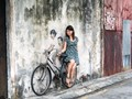 A tourist interacts with a multimedia street art painting in Penang, Malaysia.