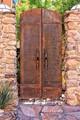 Iron door to courtyard in Bisbee, Arizona.  Handles are pickaxe heads.