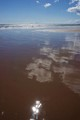 Clouds reflected in water on the beach as the tide goes out (St Cyrus, North East of Scotland)