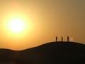 Three people on a desert sand dune